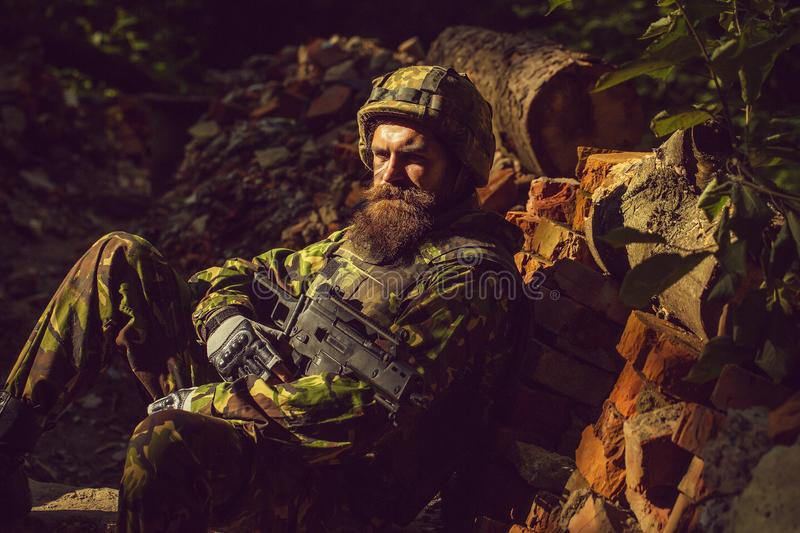 Young soldier with gun. Young soldier with sad bearded face in military helmet and camouflage with gun on ruined bricks background in forest stock image