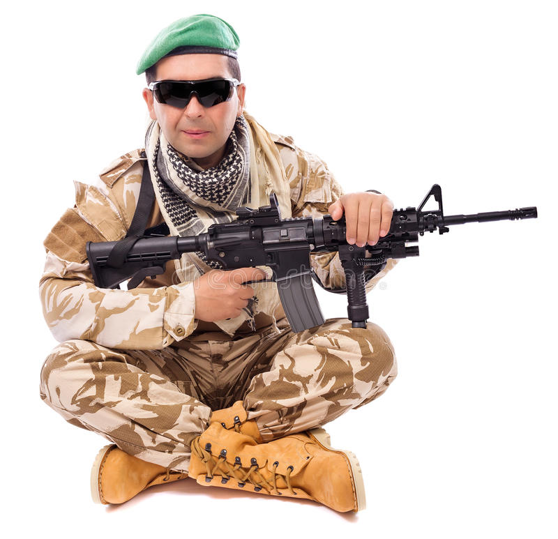 Young soldier with a gun sitting cross legged. On white background stock images