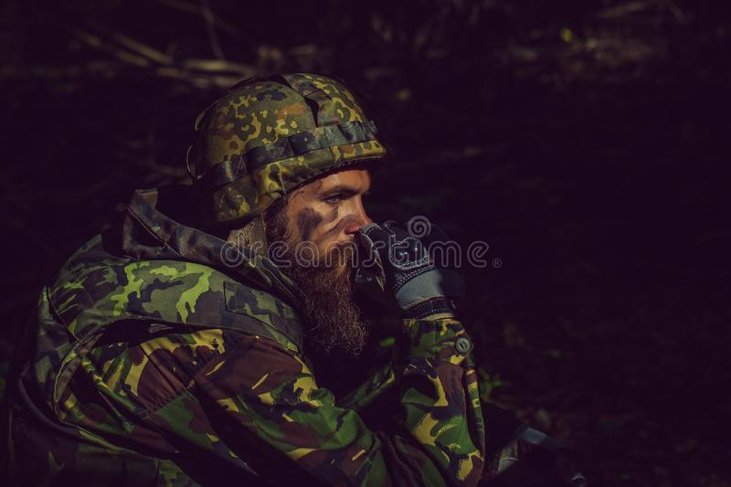 Young soldier with gun. Young soldier with sad bearded face in military helmet and camouflage with gun on forest background stock photo