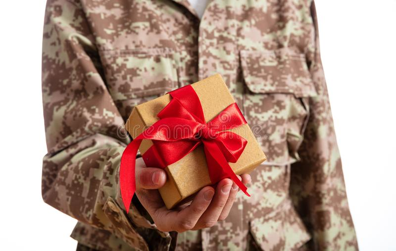 Young soldier holding a christmas gift standing on white background royalty free stock images
