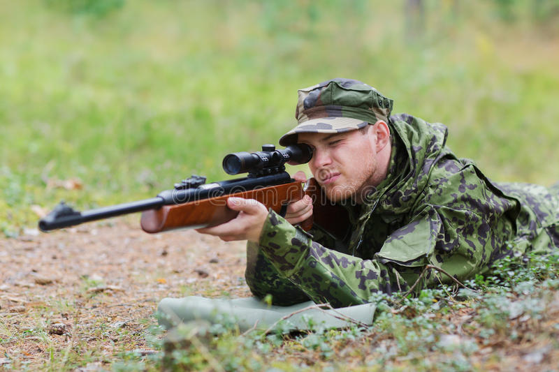Young soldier or hunter with gun in forest. Hunting, war, army and people concept - young soldier, ranger or hunter with gun aiming and shooting in forest royalty free stock images
