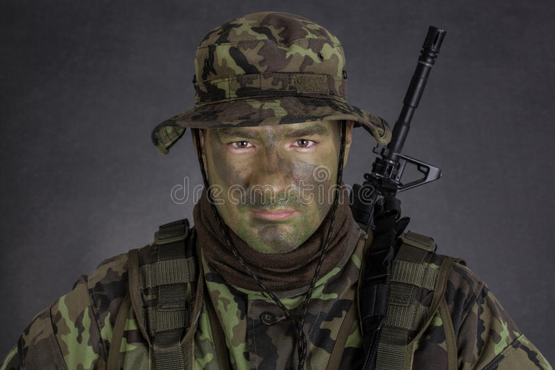 Young soldier with jungle camouflage paint. Young soldier with jungle camouflage paint on black background royalty free stock photos