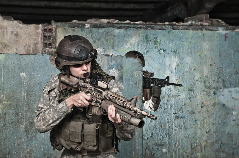 Young soldier on patrol. In ruined building, aiming. air soft gun player royalty free stock image