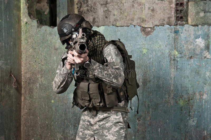 Young soldier on patrol. In ruined building, aiming. air soft gun player stock photos