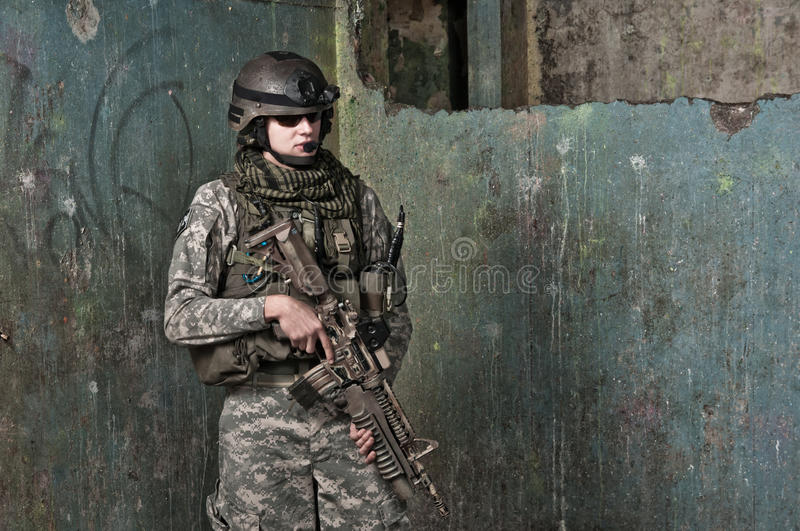 Young soldier on patrol. In ruined building. air soft gun player royalty free stock photography