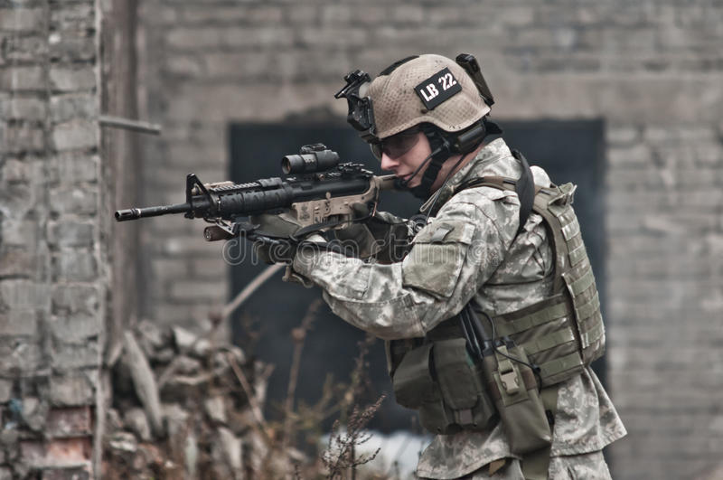 Young soldier on patrol. In open field, walking in formation, aiming. air soft gun player stock photo