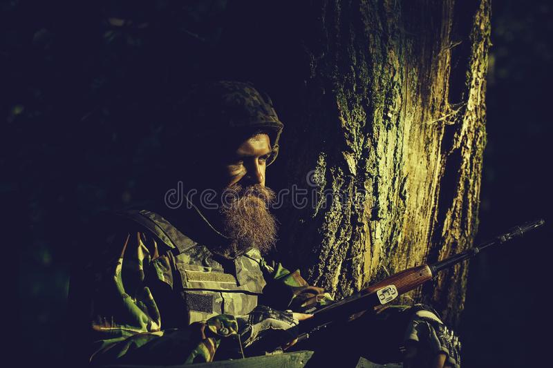 Young soldier with rifle. Young soldier with beard on dirty tired face in military uniform and helmet with rifle on tree and green forest background outdoor royalty free stock images