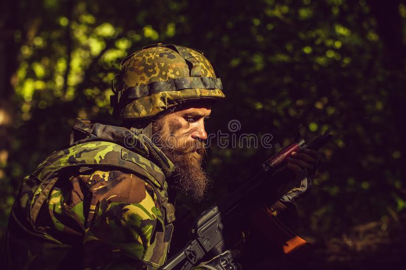 Young soldier with gun. Young soldier with sad bearded face in military helmet and camouflage with gun on forest background stock photography