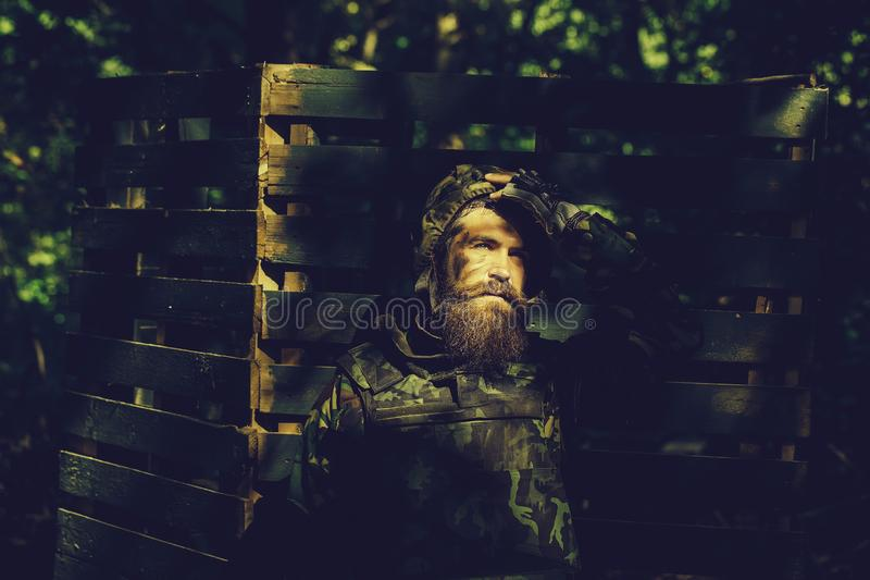 Young soldier with gun. Young soldier with sad bearded face in military helmet and camouflage with gun on wooden background stock photo