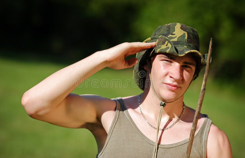 Young soldier salute. Young soldier in khaki cloth salute outdoor royalty free stock images