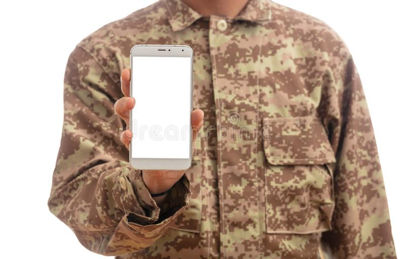 Young soldier showing a mobile phone with blank screen on white background stock photography