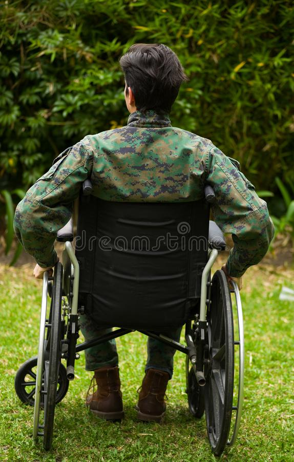 Young soldier sitting on wheel chair at outdoors in the patio, touching with his hands the wheels and giving a back, in. A backyard background royalty free stock images