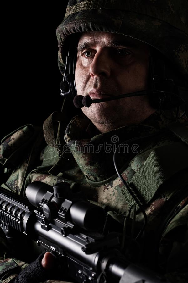 Soldier special forces with rifle on dark background. Young Soldier special forces with rifle on dark background stock photo