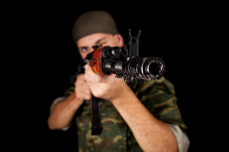 Young soldier in uniform with rifle. Selective focus on weapon stock photography