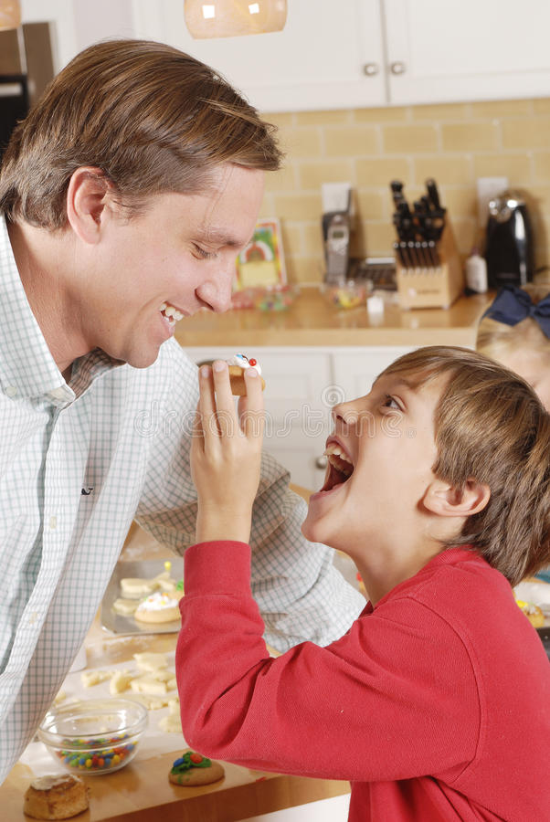 Young son feeding dad a cookie in the kitchen royalty free stock photo
