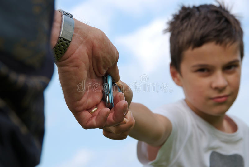 Young son fighting over a cellphone royalty free stock image