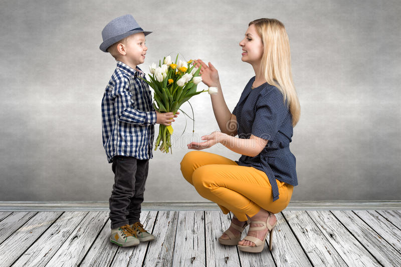 Young son gives his beloved mother a bouquet of beautiful tulips. Spring, concept of family vacation. Women`s day. stock photo