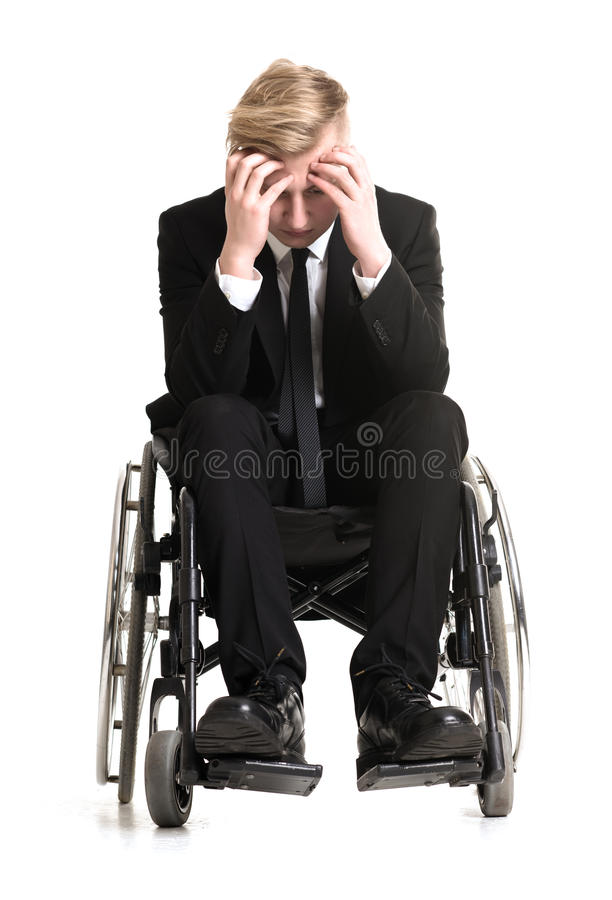 Young sorrowful businessman in a wheelchair royalty free stock image