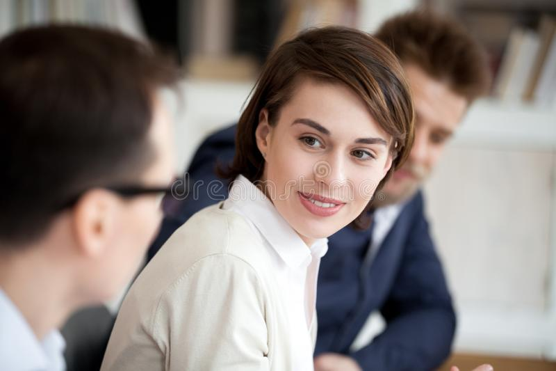 Young specialists sharing information sitting together in boardroom royalty free stock image