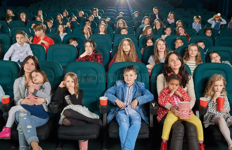 Children and teens watching film in cinema. Young spectators sitting in modern movie theatre and watching cartoon. Teenagers and children sipping fizzy drinks royalty free stock images
