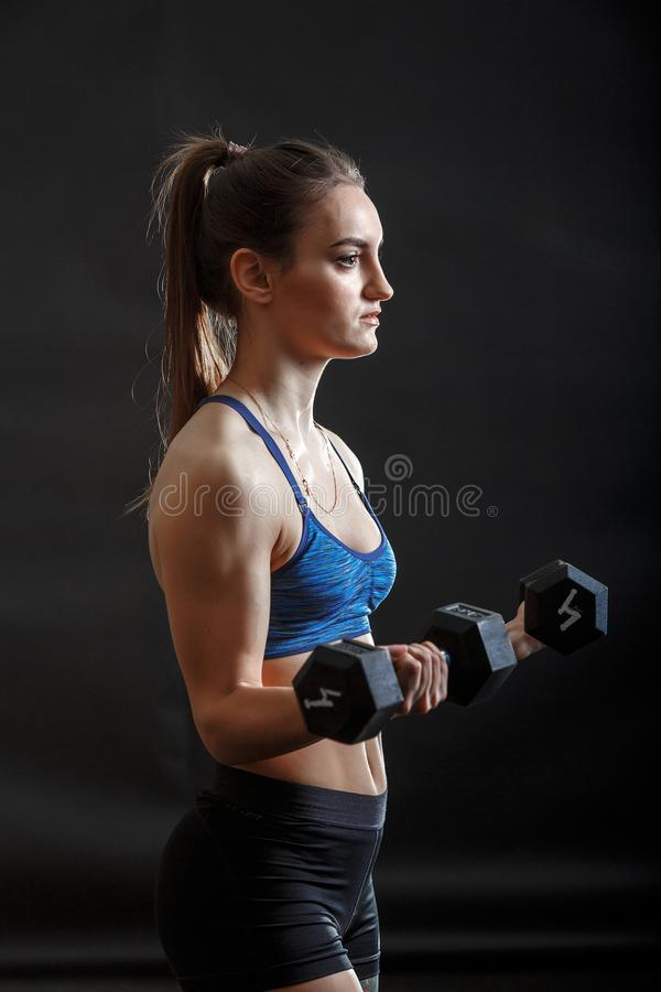 A young sport lady with ponytail in fitness clothes training with dumbells. A young attactive caucassian sport lady with brunet ponytail hairstyle in fitness royalty free stock photo