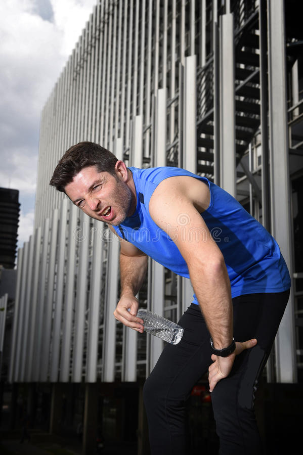 Young sport man breathing exhausted after running leaning tired. Young sport man breathing exhausted after running training on city urban background and leaning royalty free stock images