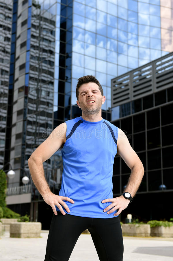 Young sport man breathing exhausted after running training on city urban background standing tired. And sweating in finished face expression in fitness and body stock photo