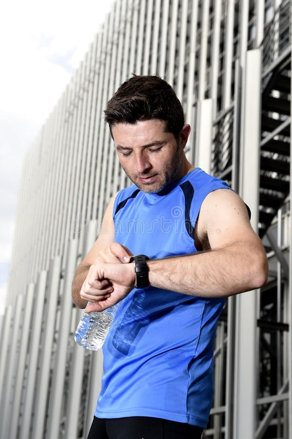 Young sport man checking time on chrono timer runners watch holding water bottle after training session. Young sport man checking time on chrono timer runners stock photography