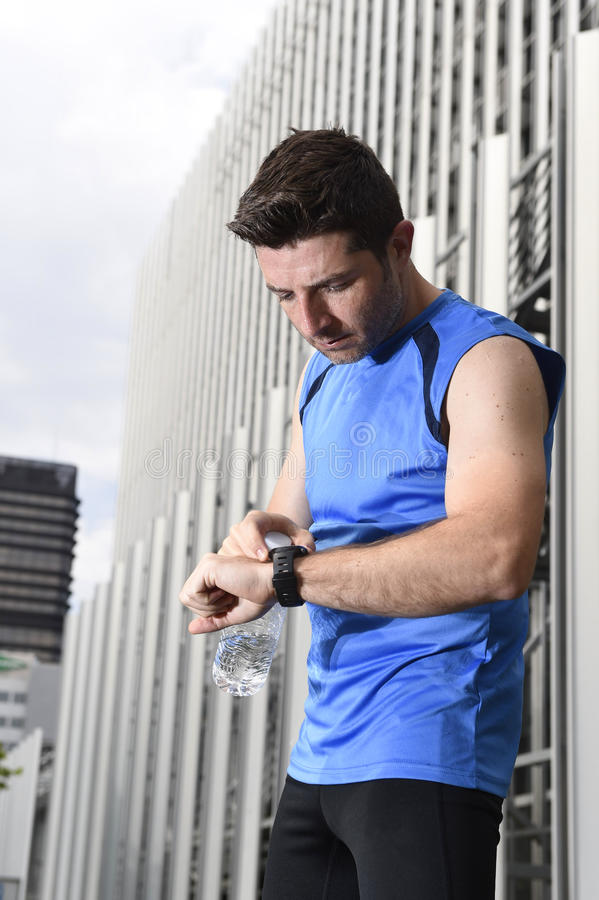 Young sport man checking time on chrono timer runners watch holding water bottle after training session. Young sport man checking time on chrono timer runners stock image