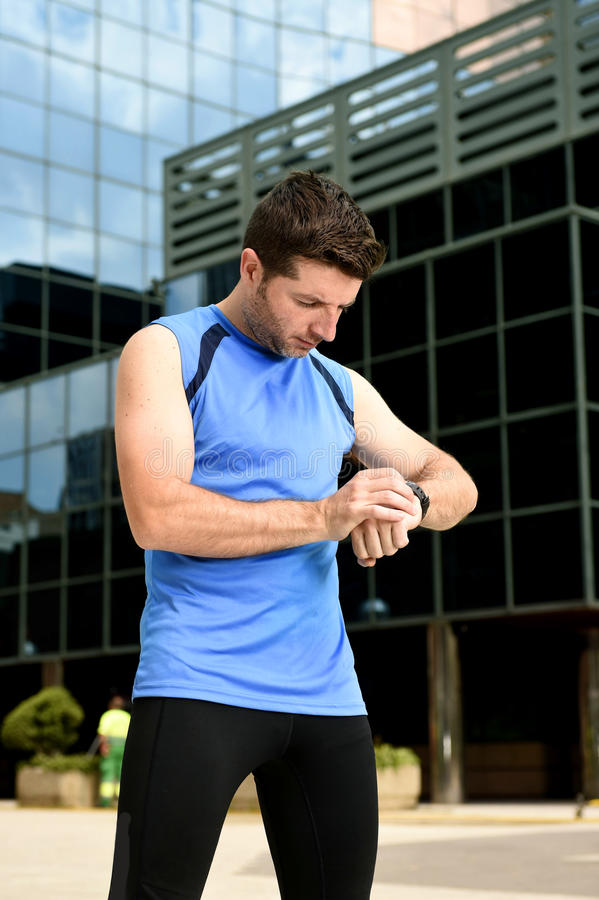 Young sport man checking time on chrono timer runners watch holding water bottle after training session. Young sport man checking time on chrono timer runners stock photos