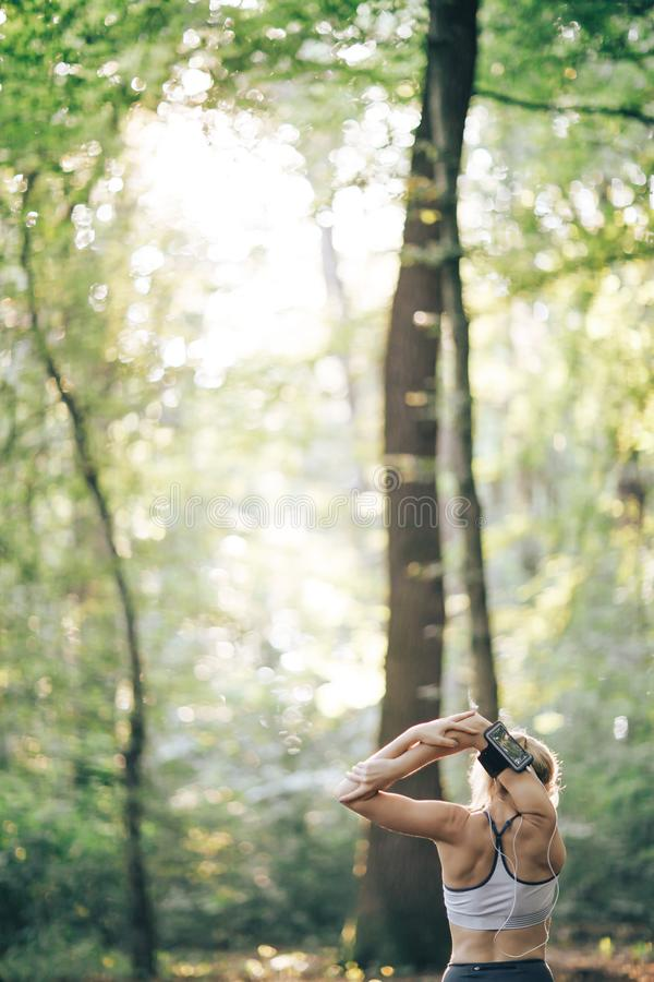 Young sport woman doing exercises during training outside in city park stock photo