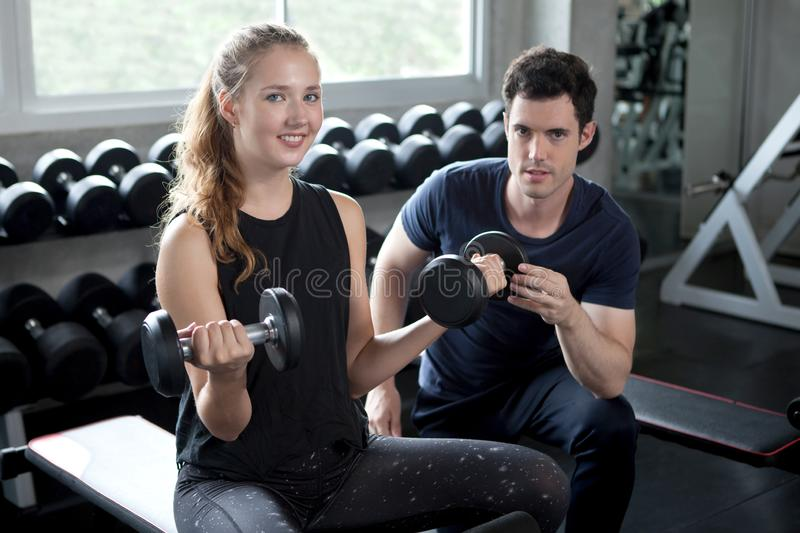 young sport woman exercise lifting dumbbells on the bench in fitness gym healthy .Muscular girl in sportswear training biceps stock photos