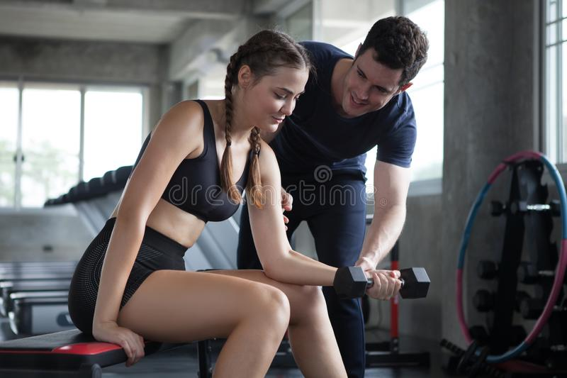 young sport woman exercise lifting dumbbells on the bench in fitness gym healthy .Muscular girl in sportswear training biceps royalty free stock photos
