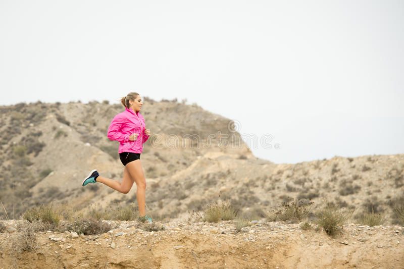 Young sport woman running off road trail dirty road with dry desert landscape background training hard. Young attractive sport woman running on off road trail royalty free stock image
