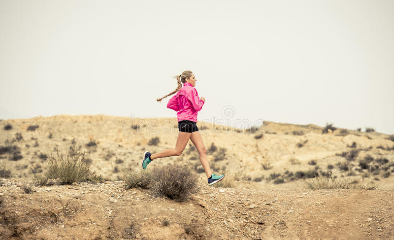 Young sport woman running off road trail dirty road with dry desert landscape background training hard. Young attractive sport woman running on off road trail royalty free stock photography
