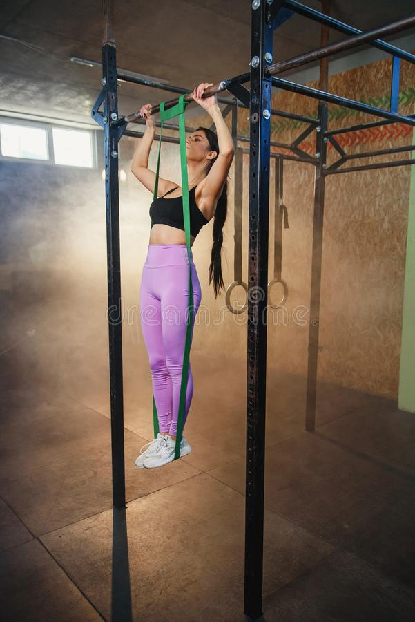 Young sport woman doing pull up in the gym. stock photos