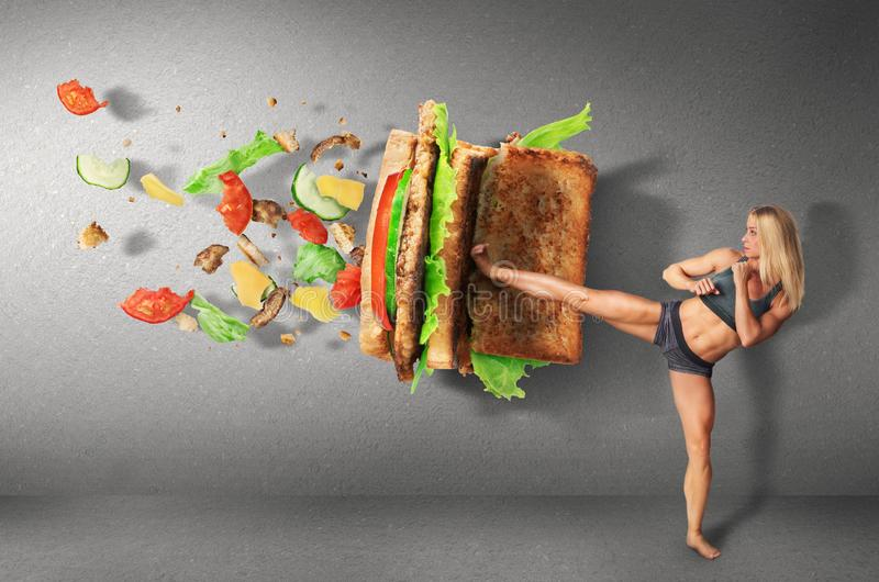 Young sport women boxing a hamburger as unhealthy food. Young sport woman boxing a hamburger as unhealthy food on a concrete wall background royalty free stock images
