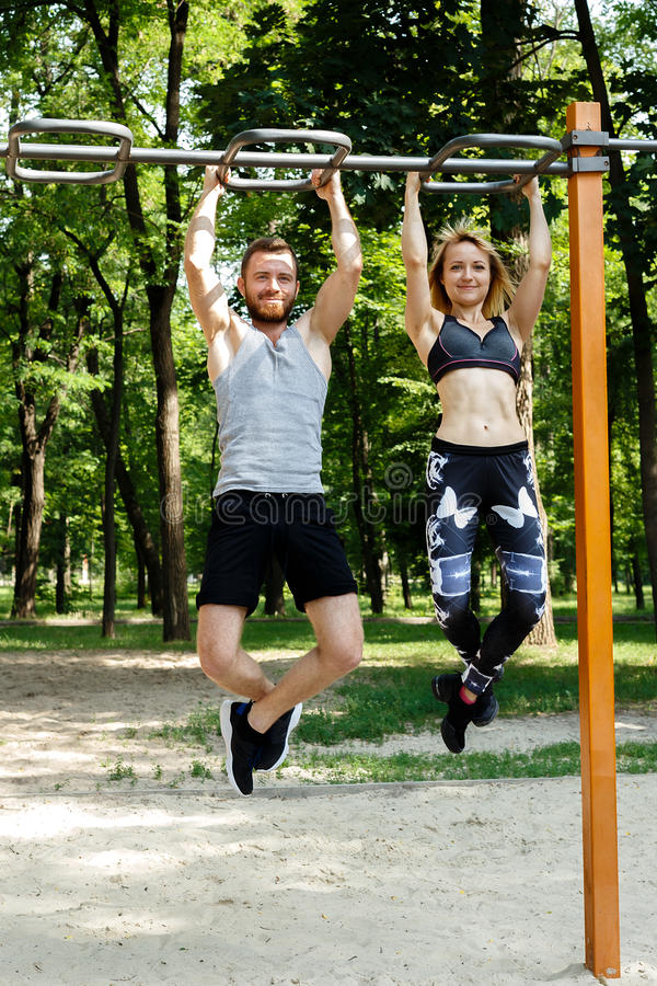 Young sportive couple doing pull-ups exercises on crossbar in a. Parrk at summer day stock photography