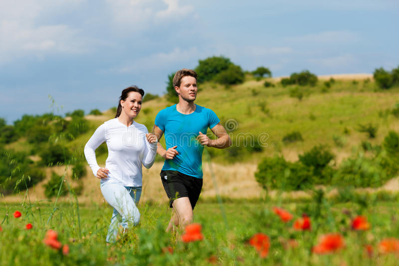 Young sportive couple is jogging outside stock photos