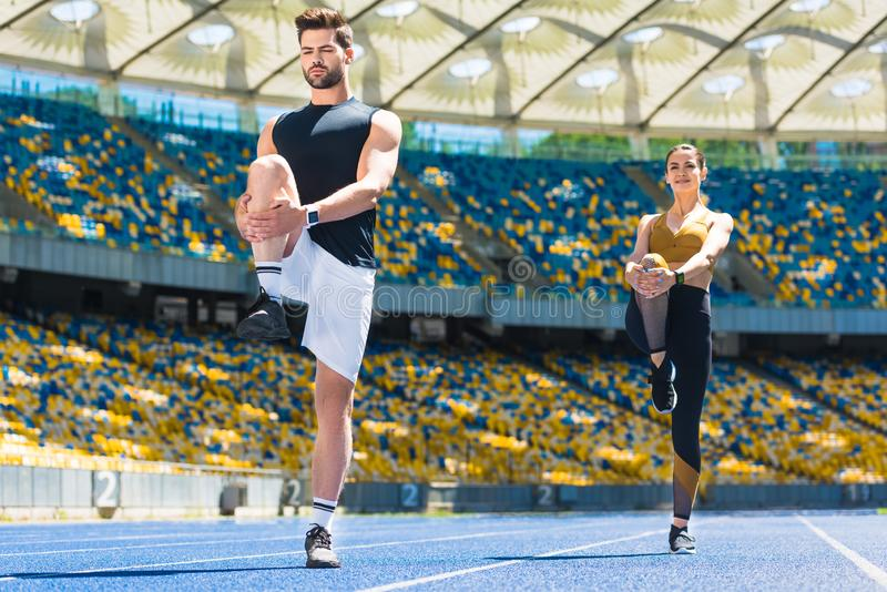 young sportive couple warming up legs before jogging on running track royalty free stock images