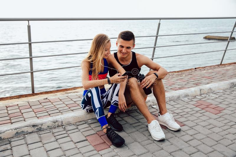 Young sportive couple watching a video on cell phone, while sitting on the ground royalty free stock photos