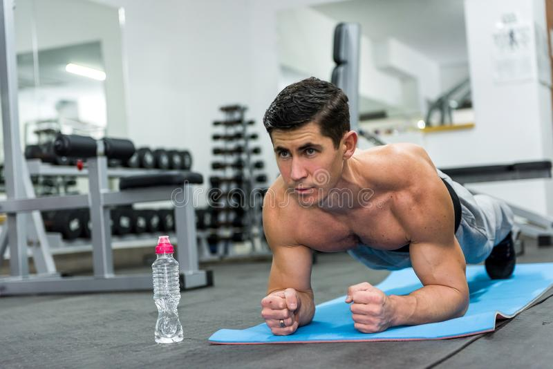Young and sportive man doing plank exercise in gym royalty free stock photography