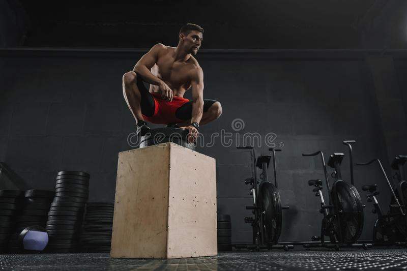 Young sportive man resting after box jump exercise at the gym. Copy space stock image