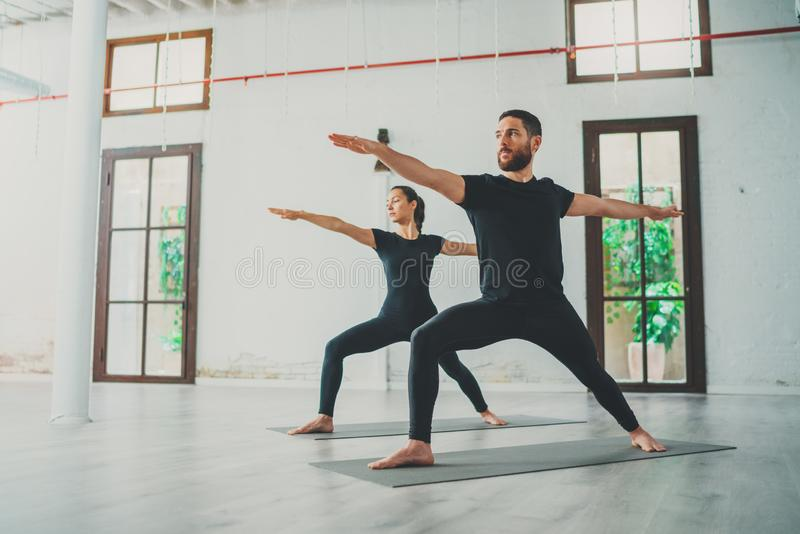 Young sportive man and woman are practicing yoga exercises in the studio. Couple of young sporty people practicing yoga stock photography