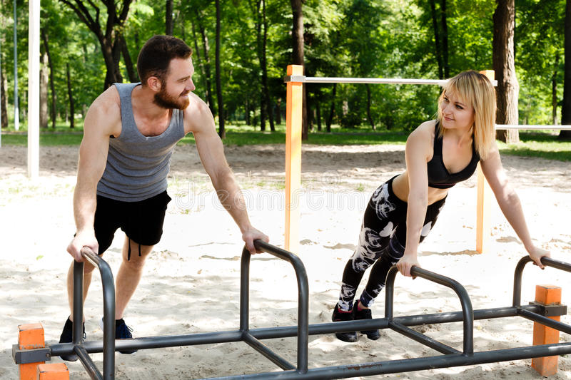 Young sportive woman and bearded man doing push-ups exercises. Young sportive women and bearded men doing push-ups exercises in a parrk at summer day stock images