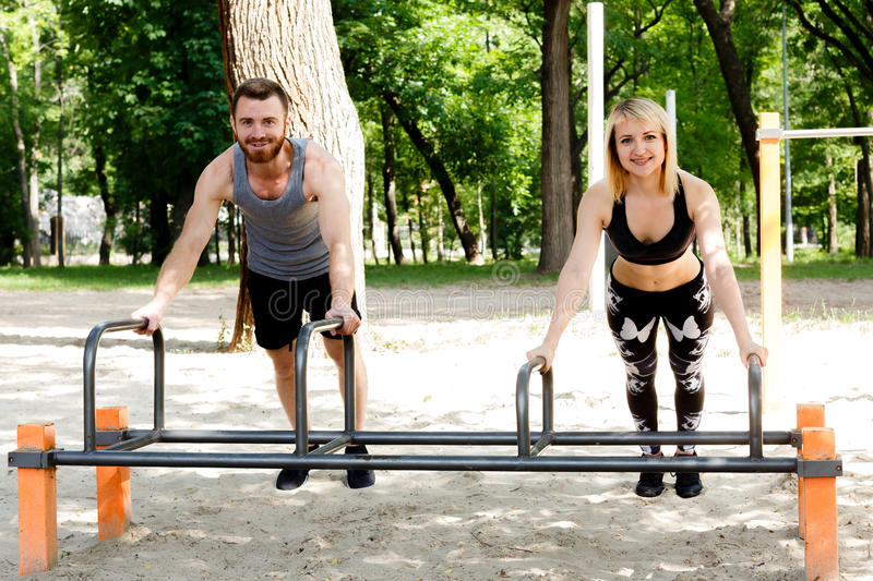 Young sportive woman and bearded man doing push-ups exercises in. Young sportive women and bearded men doing push-ups exercises in a parrk at summer day royalty free stock photos