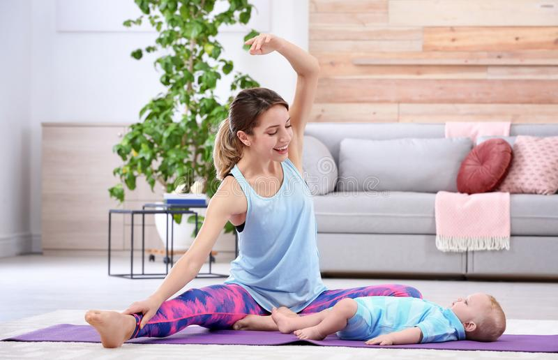 Young sportive woman doing exercise with her son at home. Fitness training stock image
