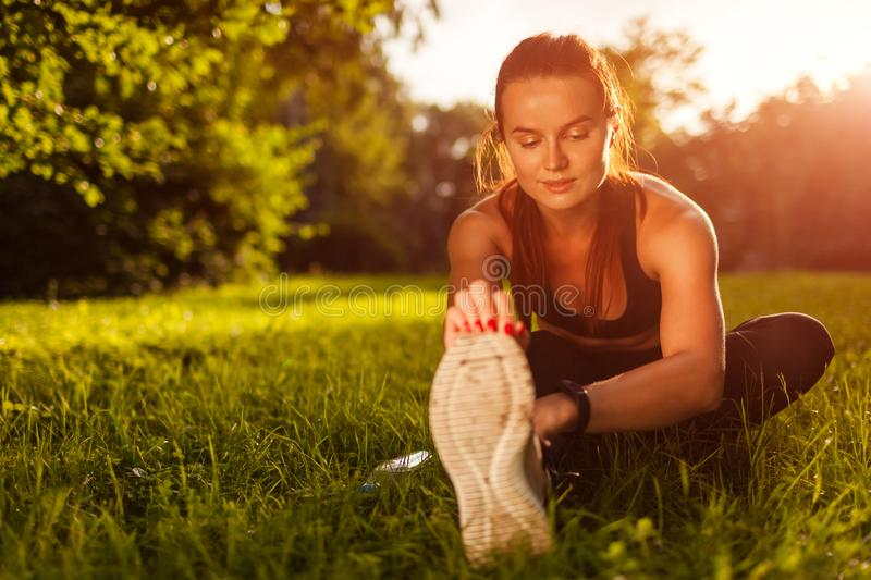 Young sportive woman doing exercises in summer park. Sportswoman stretching her legs sitting on grass. Sport concept royalty free stock photos
