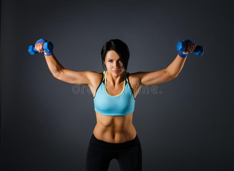 Young sportive woman with dumbbells at grey background stock images