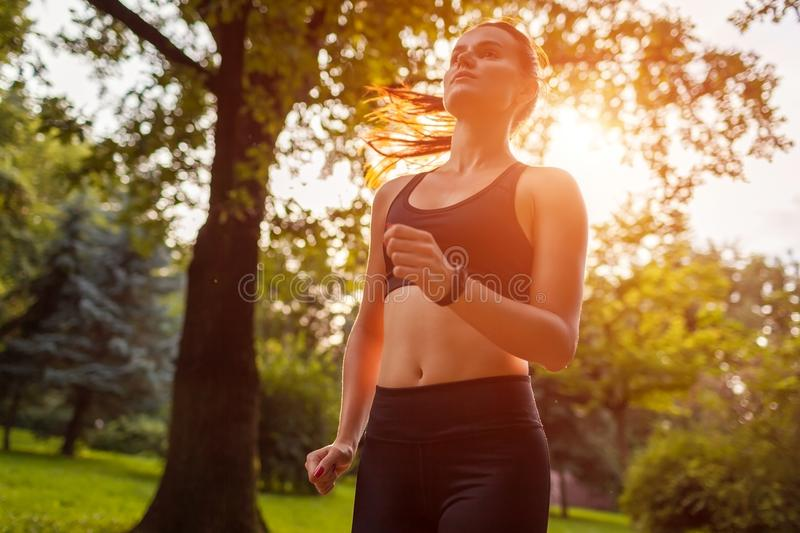 Young sportive woman running in summer park. Sportswoman jogging royalty free stock image